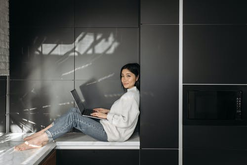 Woman in White Sweater Sitting on a White Counter Top