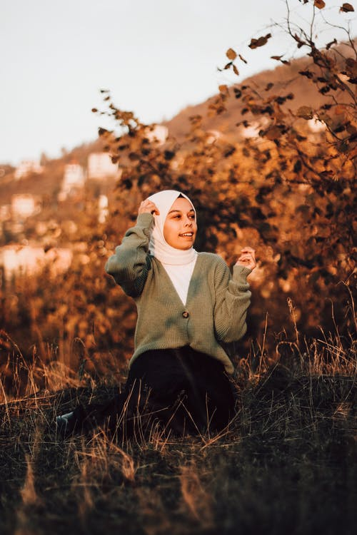 Woman in Hijab Sitting on the Grass