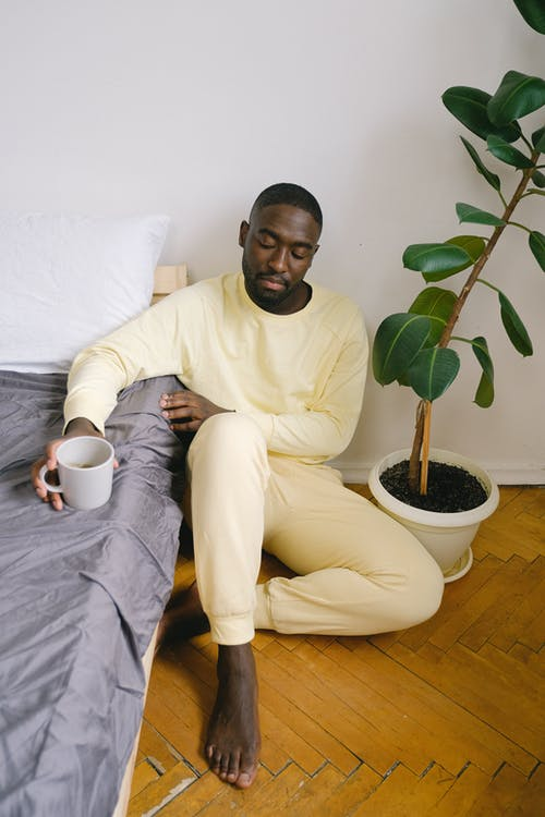 Sad African American male in pajamas sitting on floor with crossed legs and mug of hot drink at home