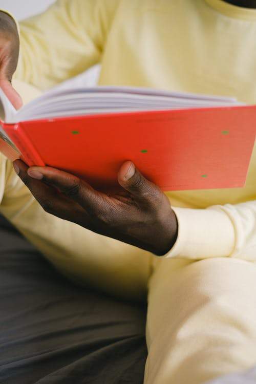 A Person Holding a Red Book