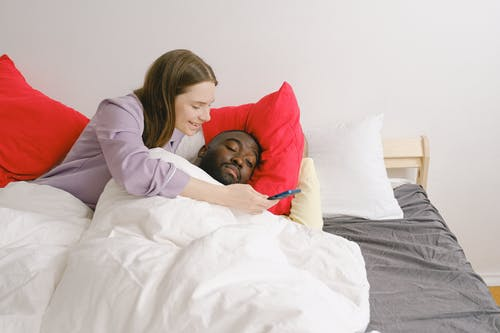 Woman Showing Mobile Phone to the Man Sleeping