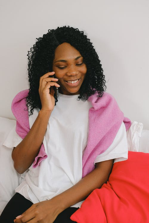 Cheerful black woman speaking on smartphone
