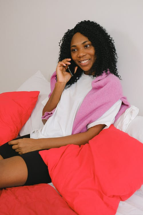 Smiling black woman having phone call in bedroom