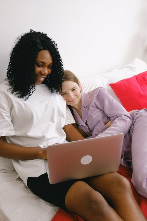 Positive multiethnic girlfriends browsing laptop on bed