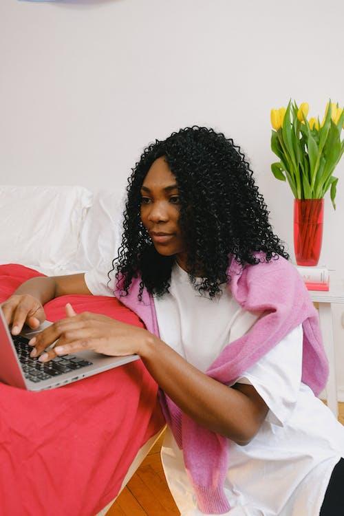 Black woman browsing laptop near bed