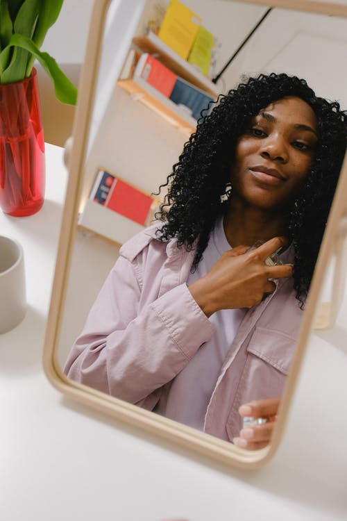 Black woman spreading perfume on neck while looking at mirror