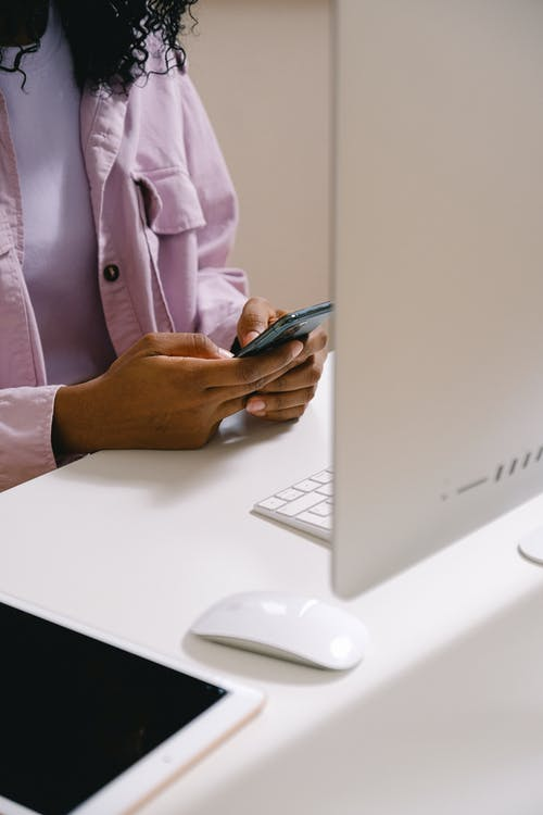 Crop unrecognizable African American female using mobile phone at white table with convenient computer in office