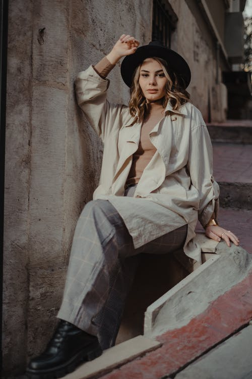 Low angle of confident female in stylish outfit touching hat while sitting on concrete border and looking at camera