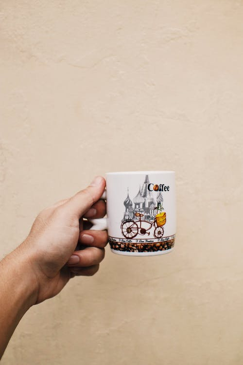 Person showing mug of hot coffee