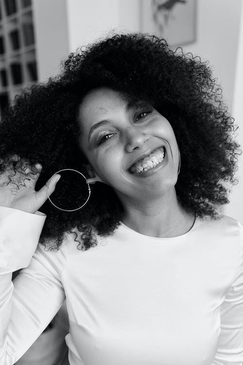 Smiling Woman in White Crew Neck Shirt Holding Her Earing