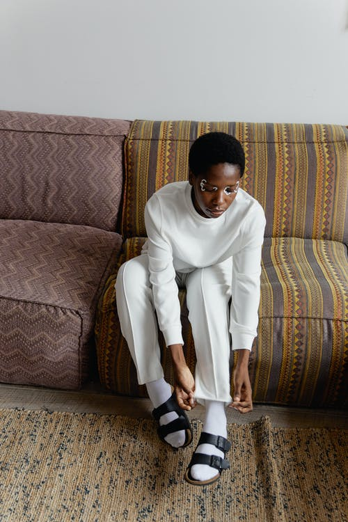 Woman in White Clothes Sitting on Brown and Beige Sofa Fixing Her Pant's Hem