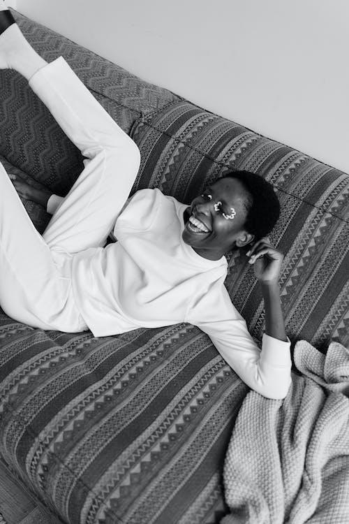 Gratis stockfoto met aan het liegen, Afro-Amerikaanse vrouw, bank