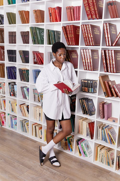 Woman in White Long Sleeves Shirt Standing Beside the Book Shelves
