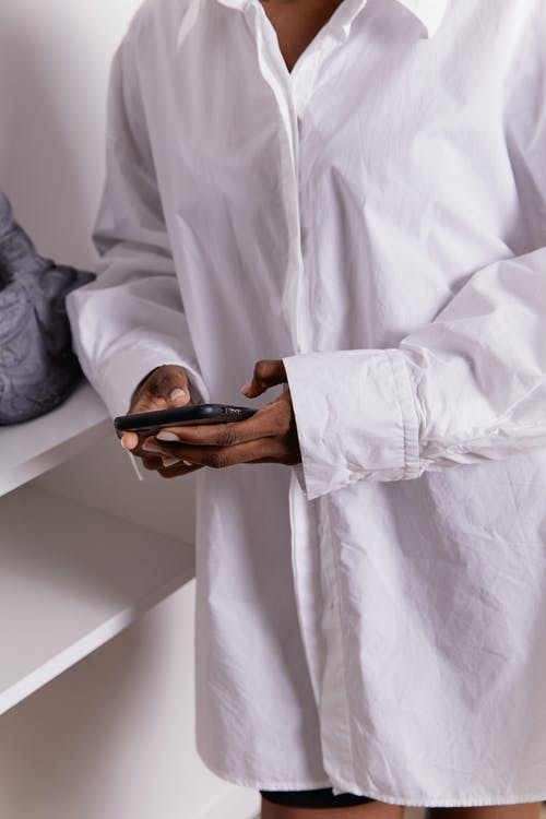 Person in White Long Sleeves Holding Mobile Phone