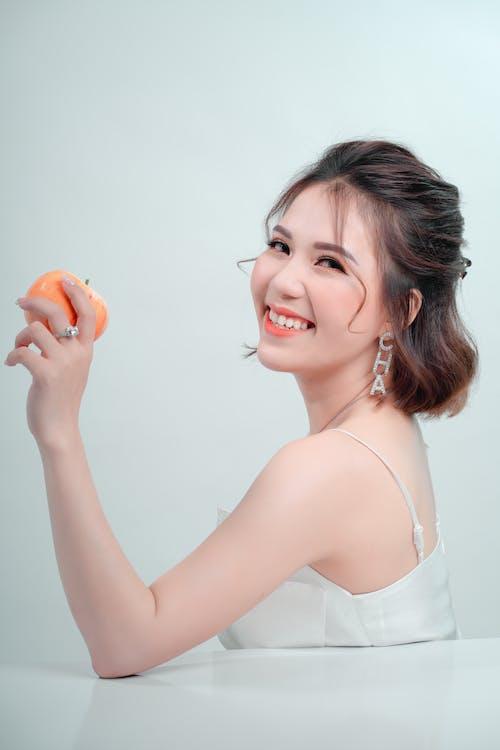 Woman in White Spaghetti Strap Top Holding Orange Fruit