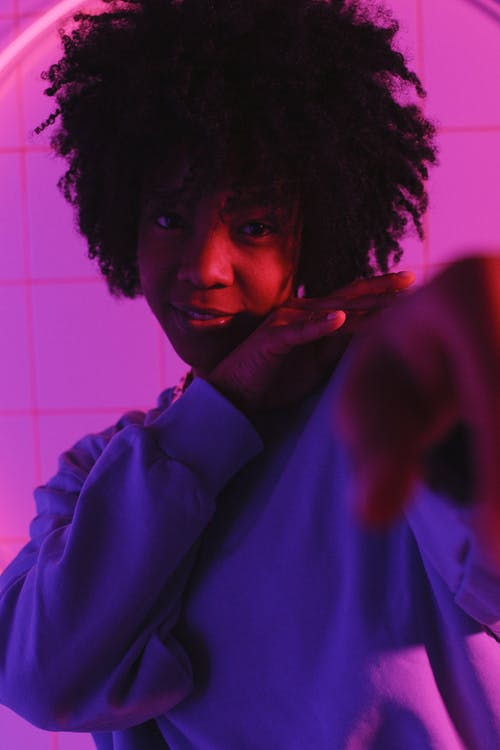 Black female with hairstyle looking at camera in room with neon lights