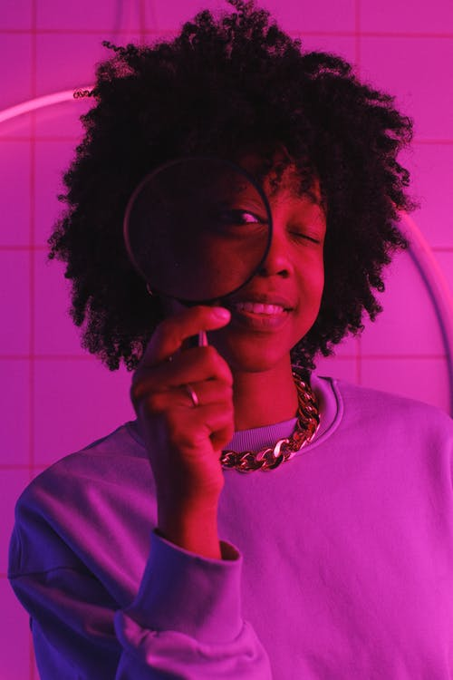 Positive African American woman with dark curly hair in casual clothes looking at magnifier in room with neon lights