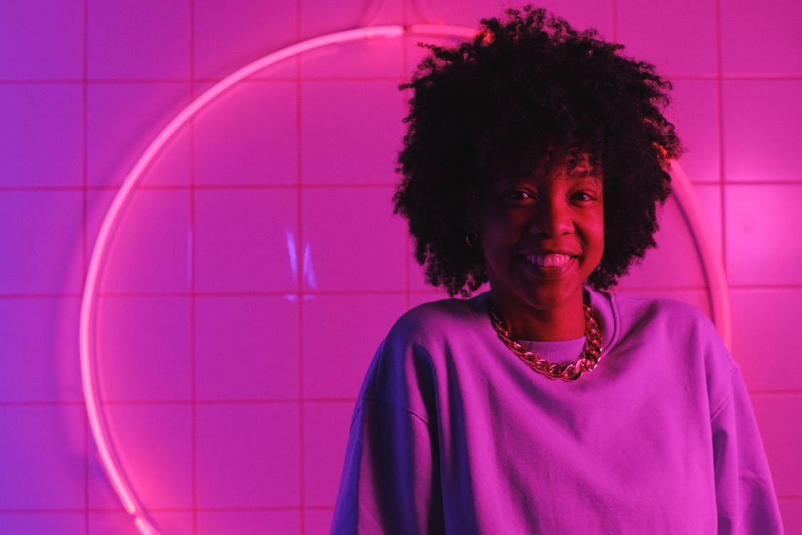 Cheerful African American woman with hairstyle in casual clothes looking at camera in room with bright pink light