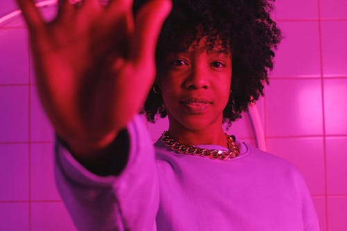 Crop trendy African American female with dark curly hair raising arm and looking at camera in room with bright pink light