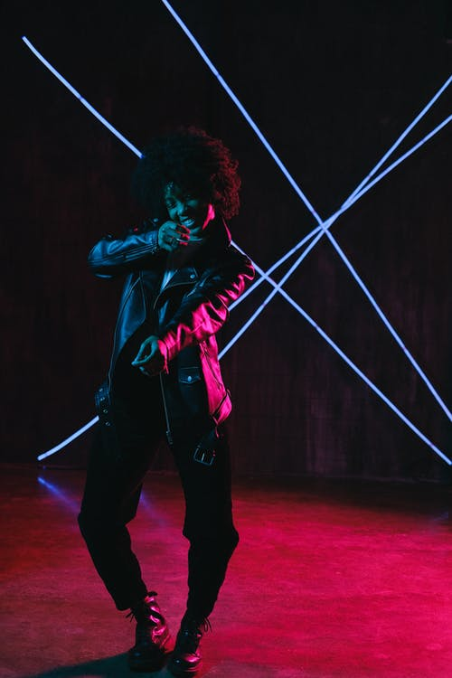 Cheerful black woman dancing in neon lights