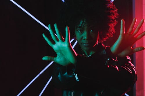 Attractive young African American female wearing trendy black leather jacket crossing arms and looking at camera while standing in illuminating neon lights in dark studio