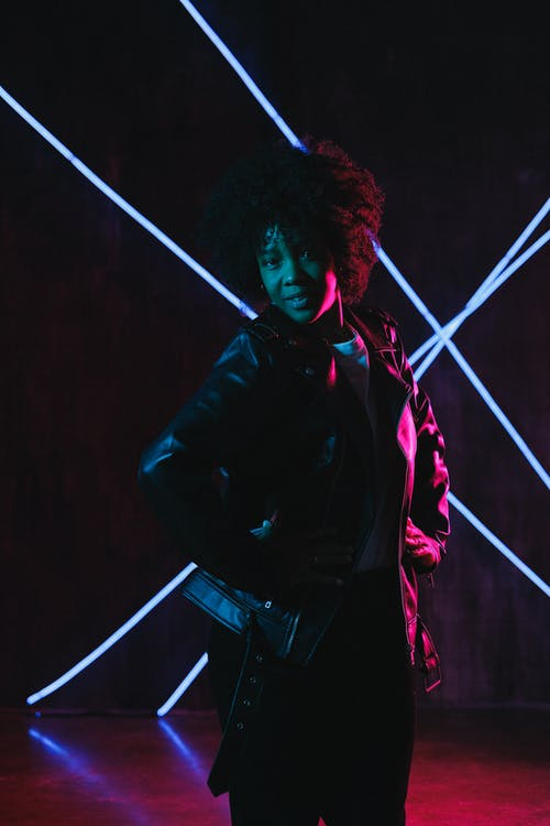 Glad young African American female in stylish leather jacket standing with hands on waist in neon lights and looking at camera