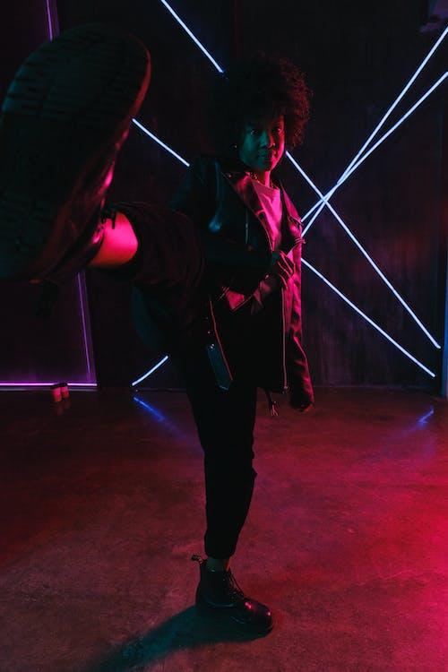 Energetic black woman kicking air in neon lights in studio