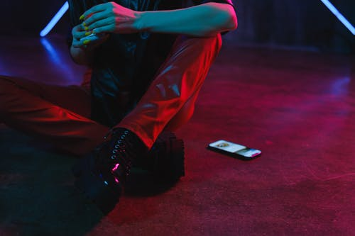 Crop faceless female wearing informal leather clothes sitting on floor near mobile phone in neon lights in dark studio