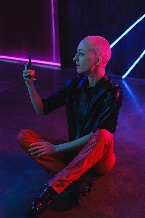 Positive bald woman browsing smartphone on studio floor