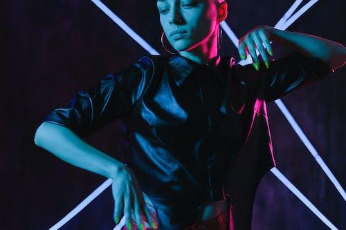 Crop woman dancing in neon lights