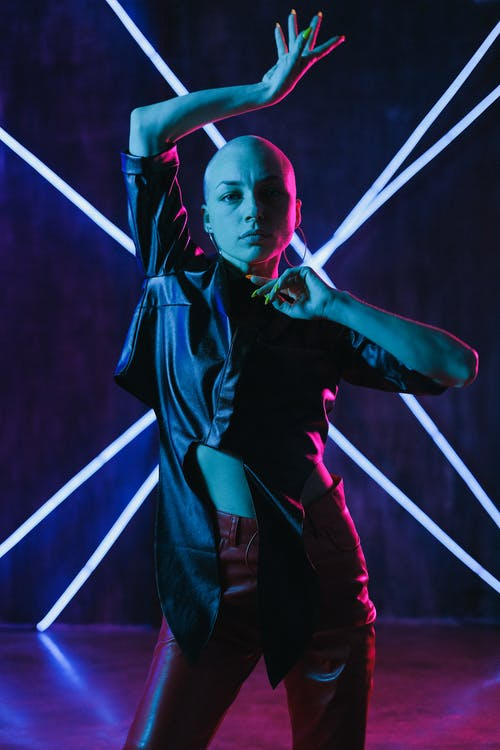 Unemotional bald female wearing leather clothes dancing with arms raised in neon studio and looking at camera