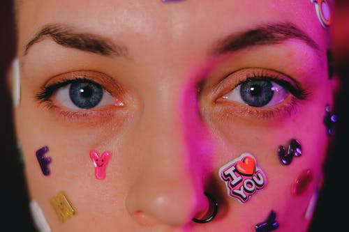 Crop calm female with nose piercing and letter stickers on face standing on dark background and looking at camera