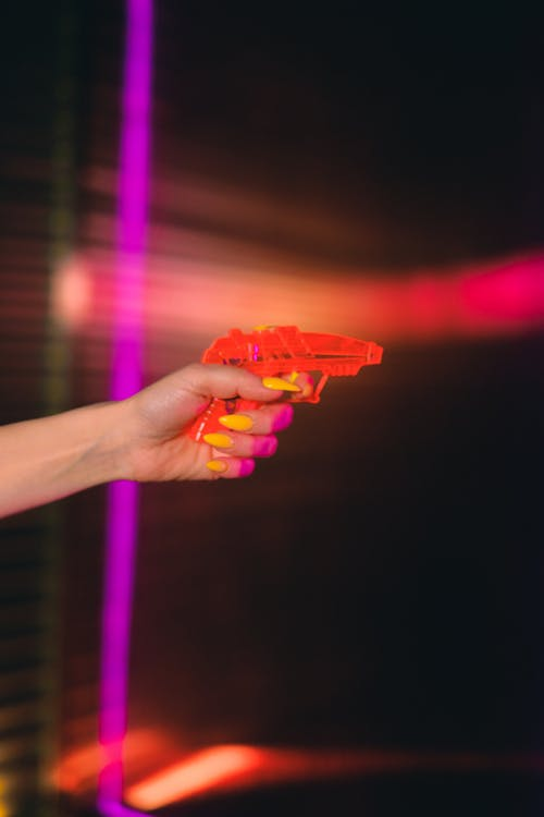 Person Holding Orange Plastic Toy Gun