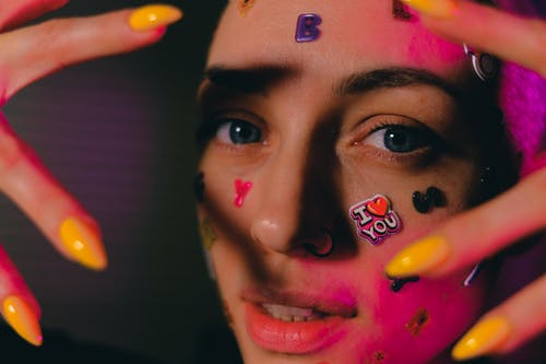 Crop bald woman with stickers on face in neon light