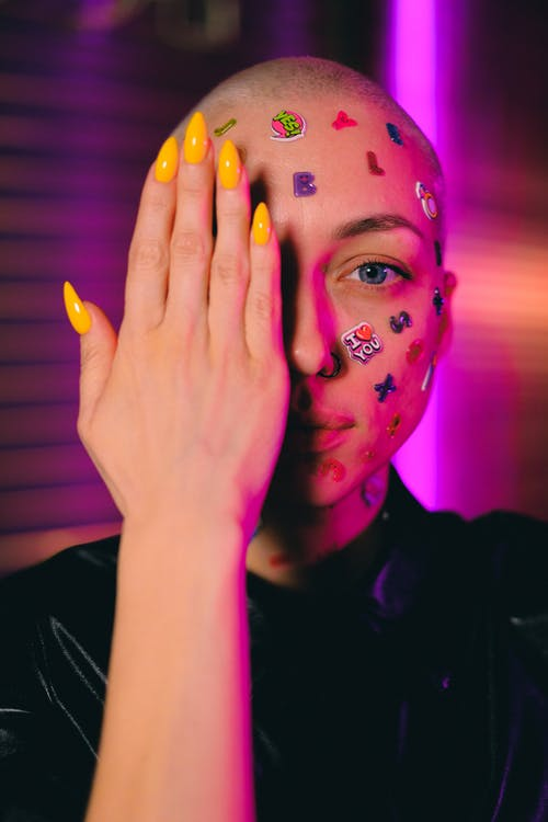 Emotionless bald female with small multicolored stickers on face covering half face with hand and looking at camera in dark studio