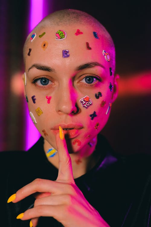 Bald woman with stickers on face showing shush sign