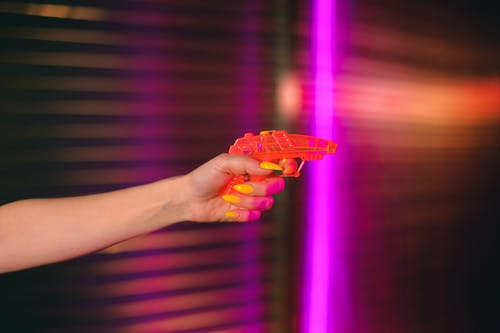 Crop anonymous female with manicured hand pointing toy gun against neon lights in dark studio