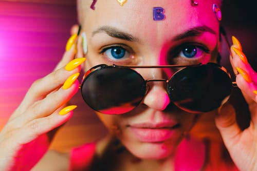 Crop bald woman with sticker on face lowering sunglasses
