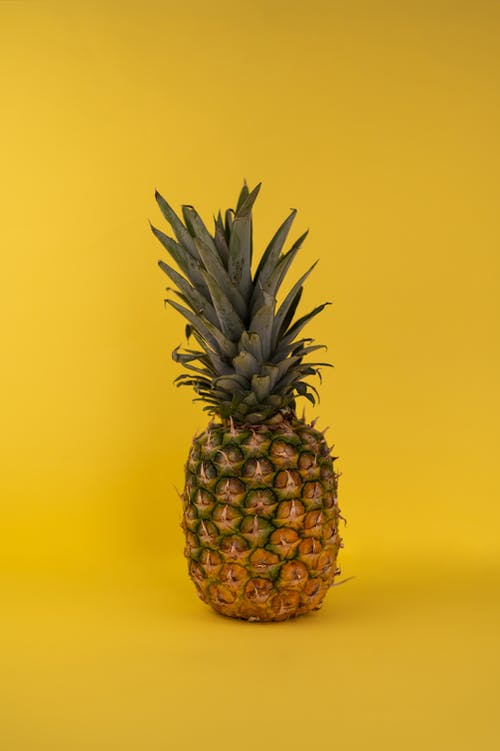 Whole fresh edible ripe pineapple fruit with green crown and brown skin placed on yellow background in modern light studio