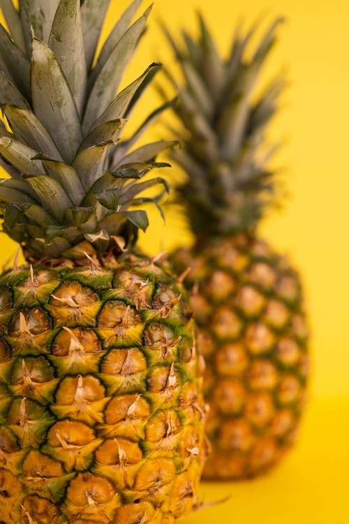 Whole ripe pineapples for healthy diet with green crowns and brown skin placed on yellow blurred background in light studio
