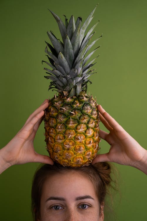 Crop unrecognizable female with fresh whole tasty pineapple on head standing on green background in light studio during ripening season