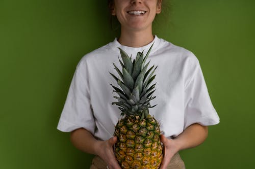 Positive crop unrecognizable female wearing casual clothes with ripe pineapple in hands smiling while standing on green background in light room