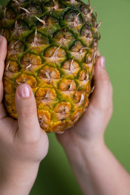 Anonymous woman with pineapple in hands