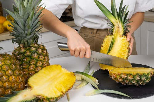 Crop anonymous cook cutting ripe pineapples with green leaves on table using big knife