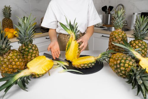 Crop unrecognizable cook demonstrating cut ripe pineapples with green leaves in kitchen