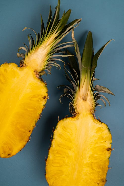 Top view of delicious fresh pineapple halves with yellow flesh and curved leaves on blue background