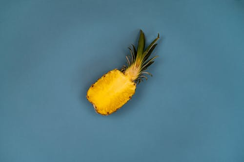 Top view of delicious cut pineapple with yellow flesh and curved green leaves on blue background