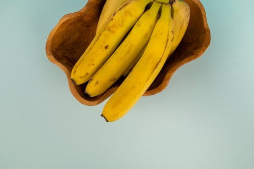 Top view of bunch of fresh bananas with blots on smooth yellow peel in curved bowl on light background