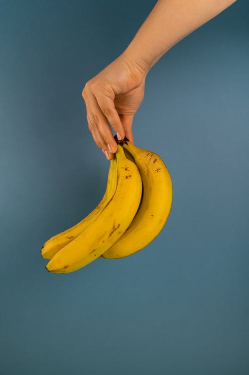 Crop unrecognizable person with bundle of delicious ripe bananas with spots on peel on blue background