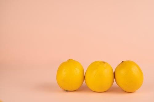 Fresh lemons in row on pastel background